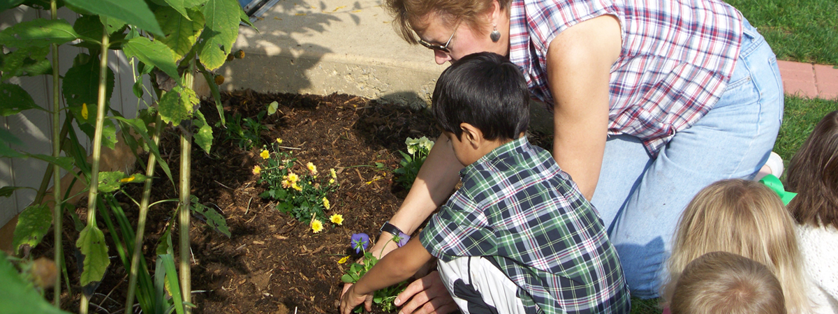 A teacher and student at the Children's School planting a garden