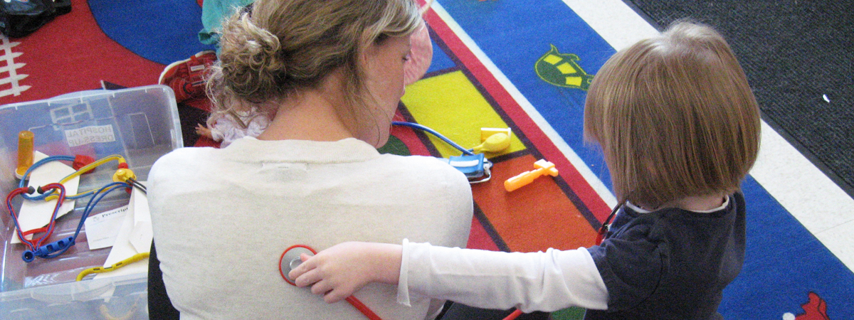 A teacher and student at the Children's School playing with a toy stethoscope