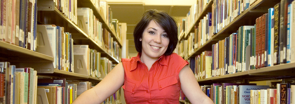A Cabrini student in library bookshelves