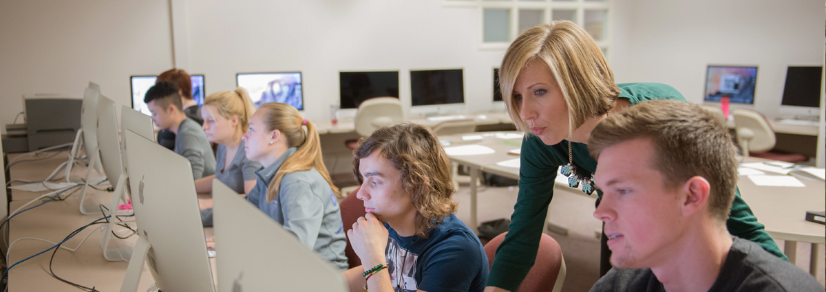 Cabrini students and Professor Jeanne Komp in a graphic design class at computer stations