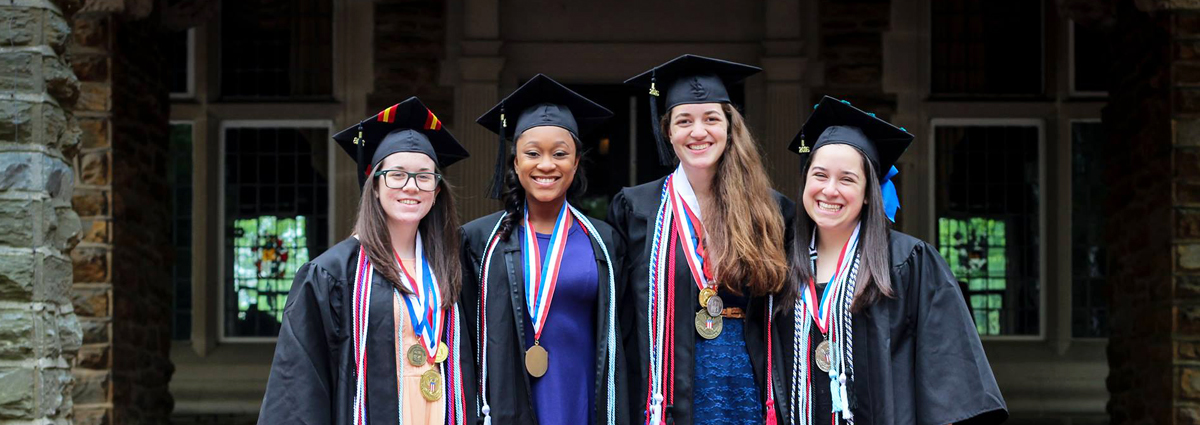 Cabrini students in caps and gowns with award medallions