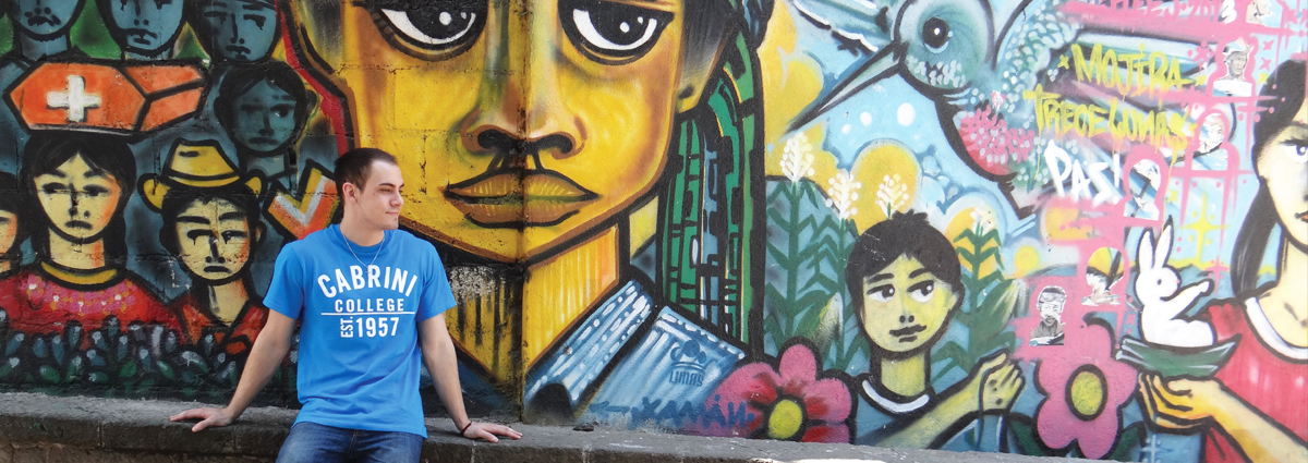 A Cabrini student in front of a mural during a study abroad trip