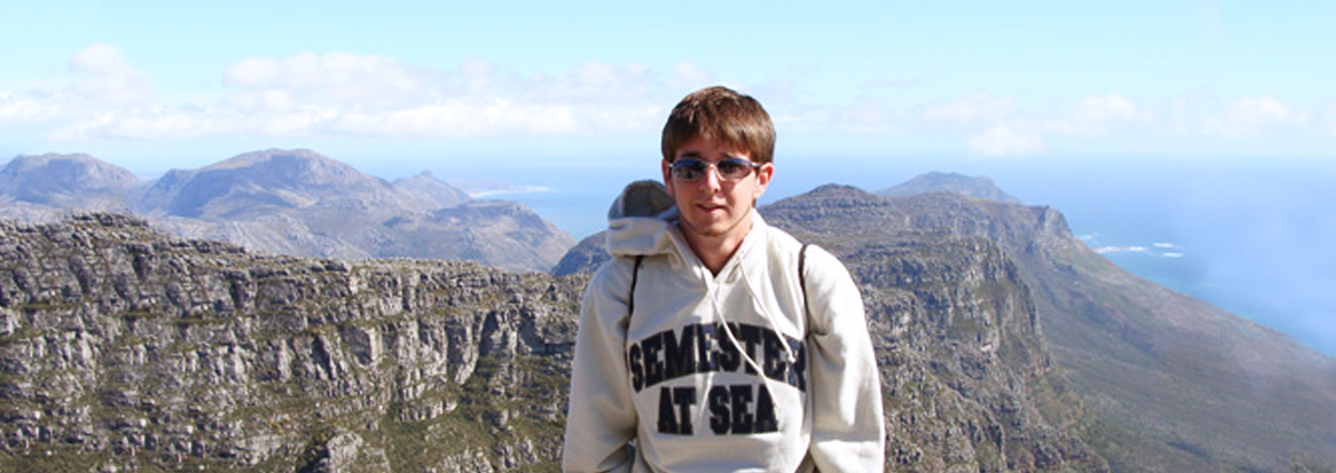 A Cabrini student wearing a Semester at Sea sweatshirt on a mountain top