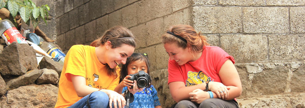 Cabrini students showing their camera to a local child during a study abroad trip