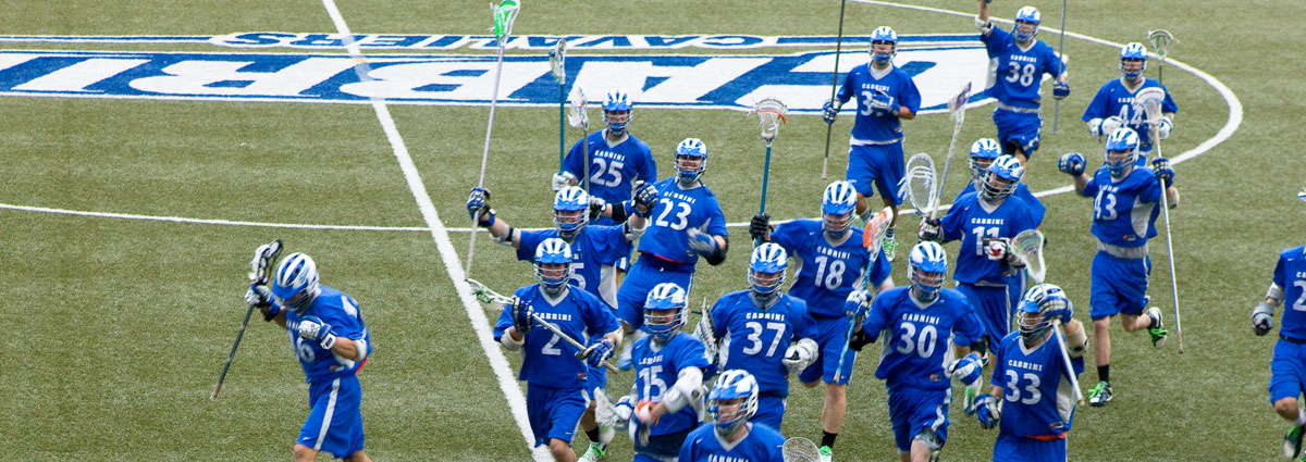 Cabrini's men's lacrosse team running across the athletic field