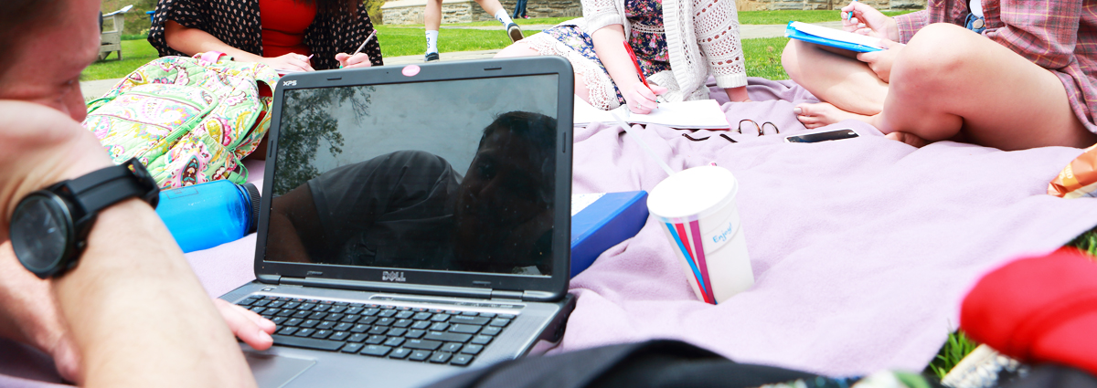 A Cabrini student on a laptop outside
