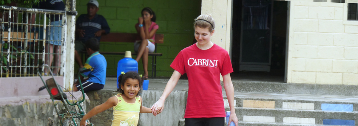 A Cabrini student with a local child in Ecuador during a service trip