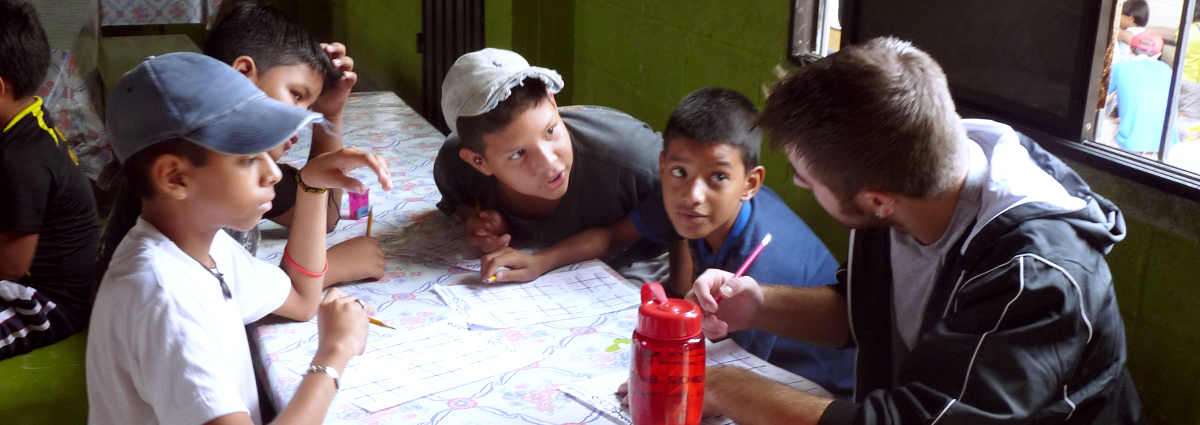 A Cabrini student with local schoolchildren in Ecuador during a service trip