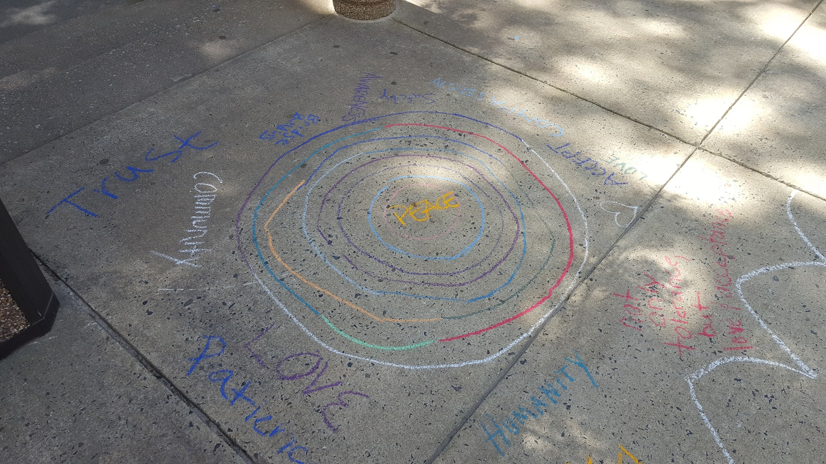 "Sidewalk chalk art showing colorful circles around the word ""Peace"""