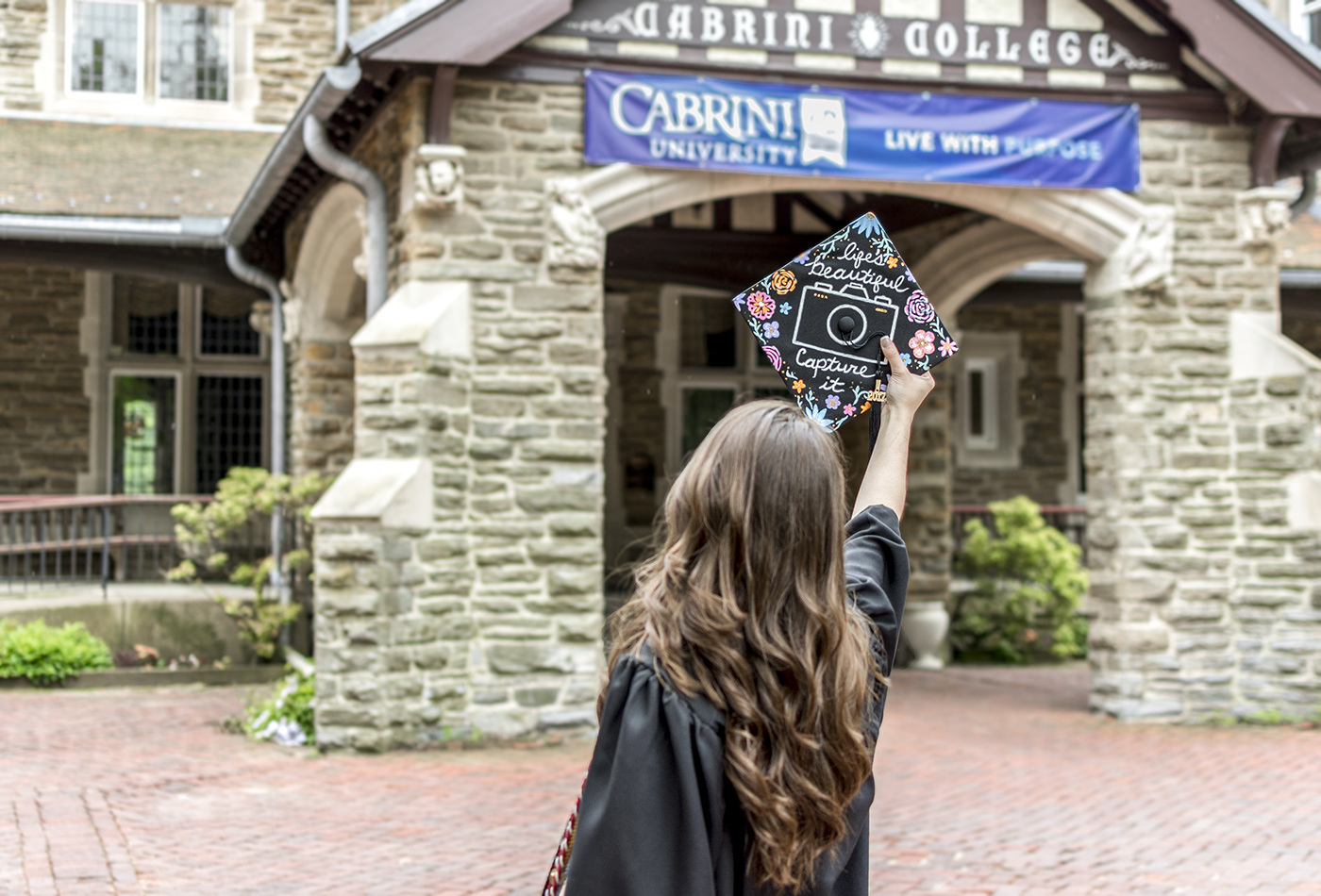 Emily holding decorated grad cap outside mansion