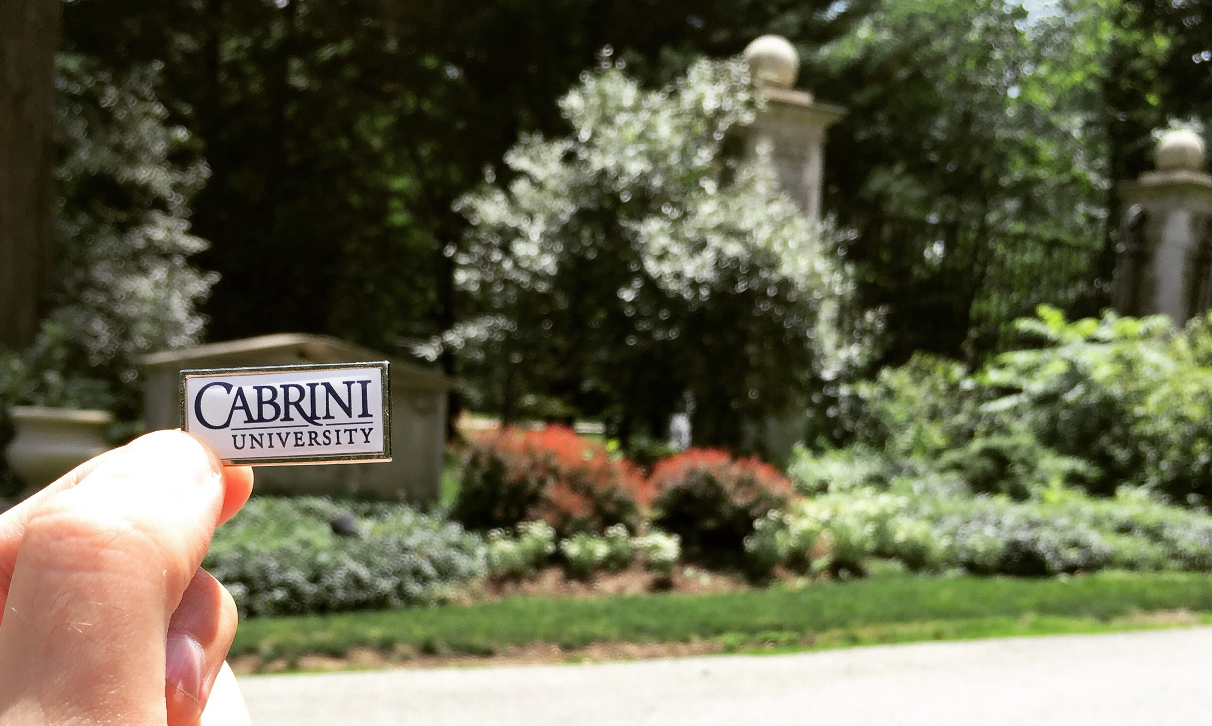 A hand holding a Cabrini University pin over the Cabrini College sign