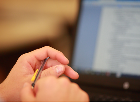 hands holding a pen, with a computer in the background