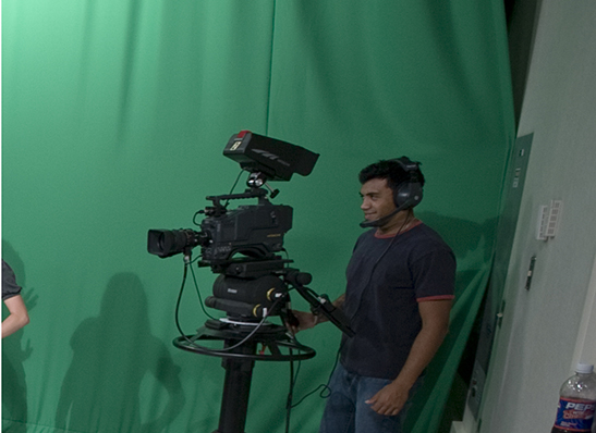 a Cabrini student with a camera in the video studio