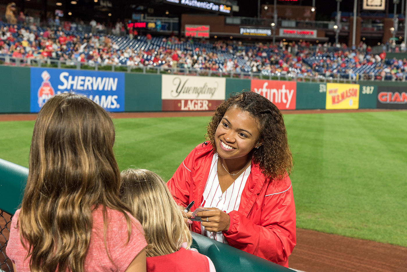 Phillies Ballgirl Jess Hayes autographs her card for fans